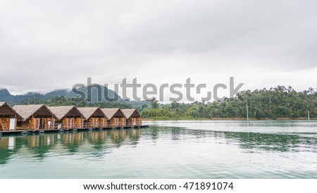 Wooden resort on the water in Ratchaprapha dam with beautiful mountain view, Surat Thani, Thailand.