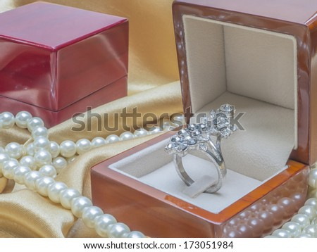 Wooden ring box with pearl necklace for wedding on silk - stock photo
