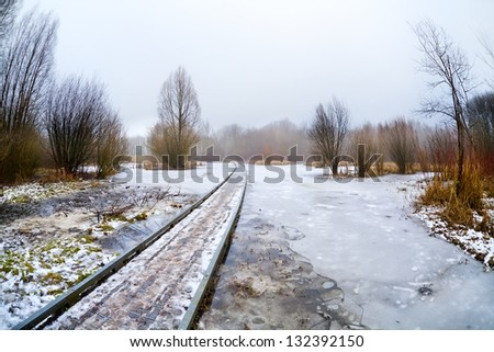 wooden road bridge through frozen lake in misty day - stock photo