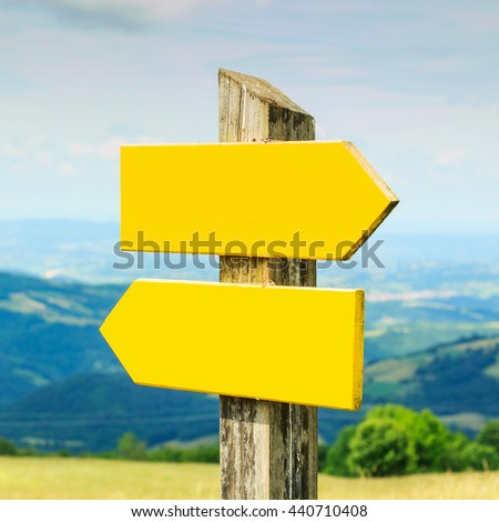 Wooden road pointer at daylight over nature background.