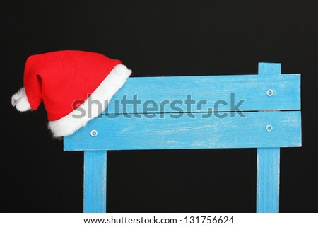 Wooden road sign with Santa hat black background