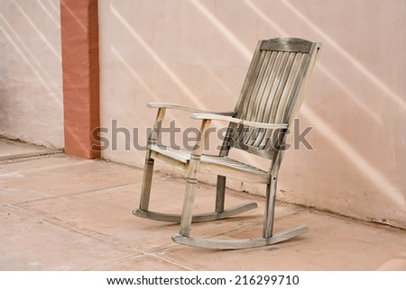 Wooden rocking chair on spanish style patio - stock photo