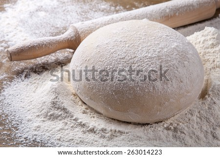 wooden rolling pin with dough and dusting of flour.