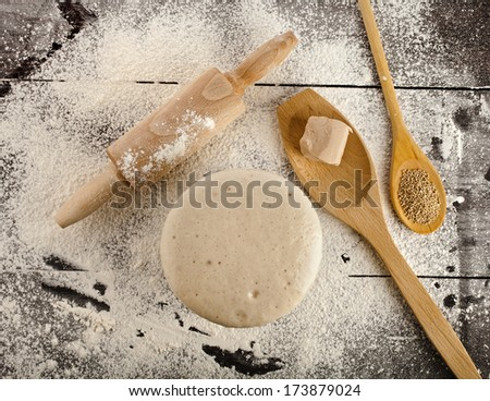 Wooden rolling pin with white wheat flour on the black surface table. top view - stock photo