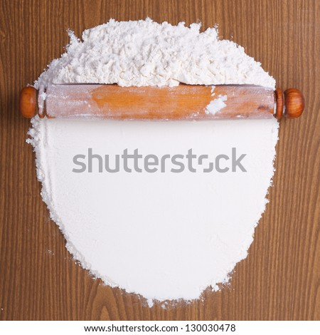 Wooden rolling pin with white wheat flour on the table. top view - stock photo