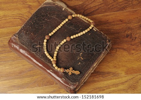 Wooden rosary and the Bible on the table   - stock photo