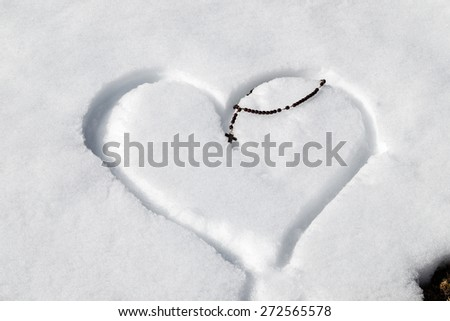 Wooden Rosary beads left on a heart drawn by hand in the fresh snow - stock photo