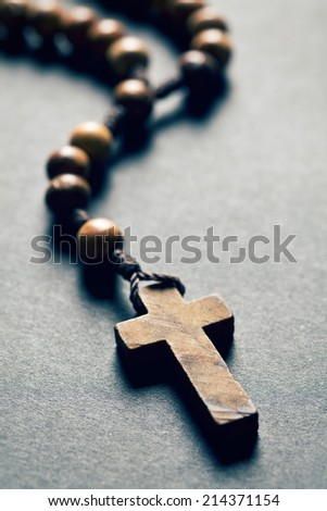 wooden rosary beads on black background - stock photo