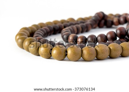 Wooden rosary different colors on white background - stock photo