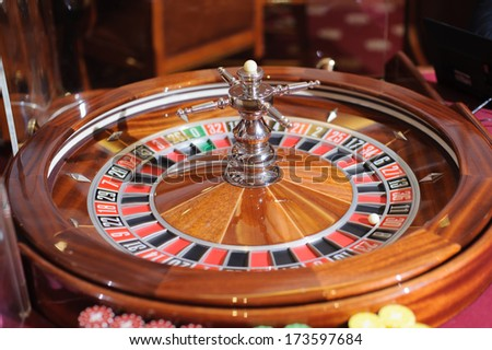 wooden roulette wheel with ball on red
