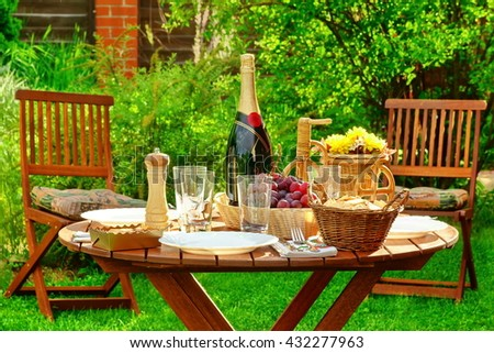 Wooden Round Picnic Table With Bottle Of Wine and Plates On The Backyard, Concept For Outdoor Seasonal or Holiday Party or Picnic