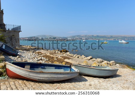 Wooden rowing boats at Swanage harbour and jetty Dorset England UK with blue sea and sky on a beautiful summer day on the English Jurassic coast - stock photo