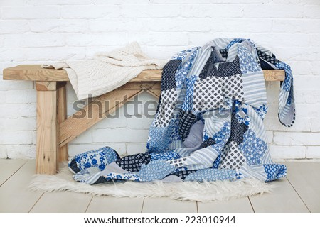Wooden rustic bench with warm cozy bedding on it - stock photo