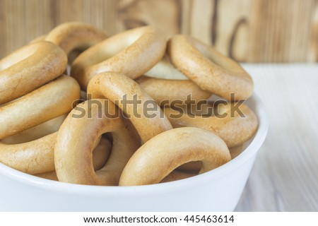 Wooden rustic table with national russian bagels in white bowl. A group of small dry bagels - stock photo