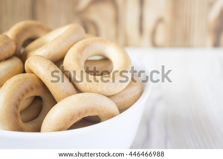 Wooden rustic table with national russian bagels in white bowl. A group of small dry bagels. Selective focus - stock photo