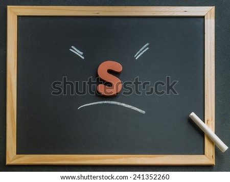 Wooden S character on black board