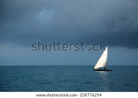 Wooden sailboat (dhow) on water with storm clouds, Zanzibar island - stock photo