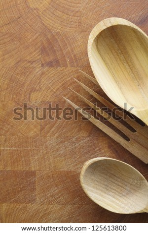 Wooden salad servers with woodgrain lying on a wood chopping board with texture, scratches and copyspace - stock photo