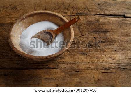 Wooden salt box with old spoon on rustic table - stock photo