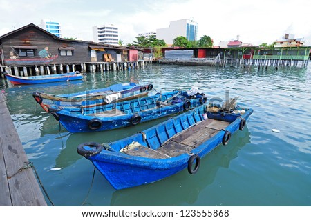 Wooden sampan boat anchored to the pier in the Chew Jetty, a UNESCO heritage site, in Penang, Malaysia. - stock photo