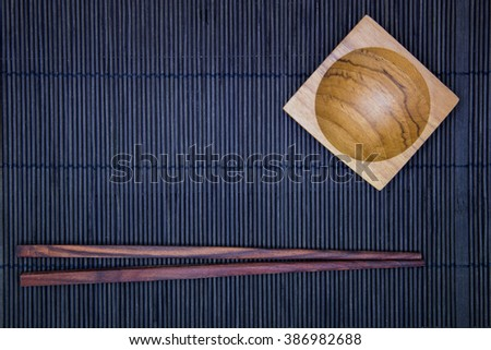 Wooden Sauce cup and chopsticks on the black bamboo mat background in top view - stock photo