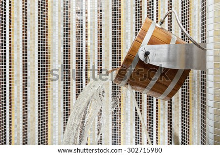 Wooden sauna bucket with spilling water in a Finnish sauna - stock photo