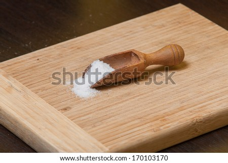 Wooden scoop filled with salt on a wooden cutting board.