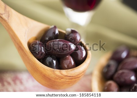 Wooden scoop of kalamata olives. - stock photo