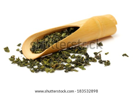 Wooden scoop over dry green tea leaves - stock photo