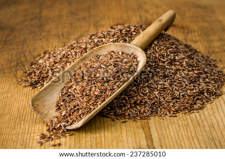 Wooden scoop with flax seeds - stock photo
