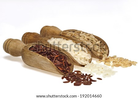 Wooden scoops with different rice types scattered on white background.
