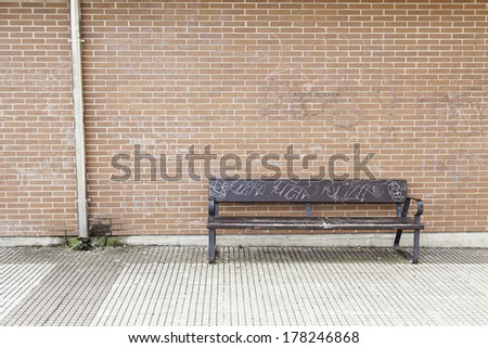 Wooden seat in the city, details of street furniture in the city bench to rest - stock photo