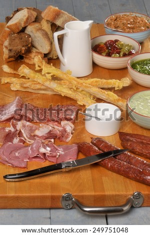 Wooden serve board with meat, bread, sauce, cheese stalk and hard sausage - stock photo