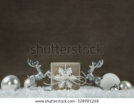 Wooden shabby style christmas background in silver, white, brown and grey colors with gift box and reindeer. - stock photo