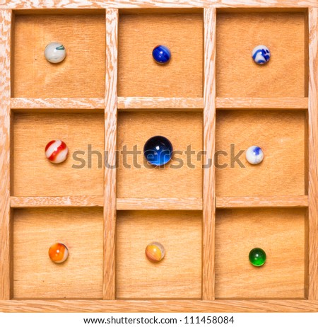 Wooden shadow box with collection of antique marbles