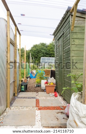 Wooden shed and polytunnel on an allotment - stock photo