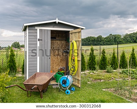 Wooden shed with different garden tools and equipment - stock photo