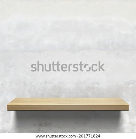 Wooden shelf on concrete wall - stock photo
