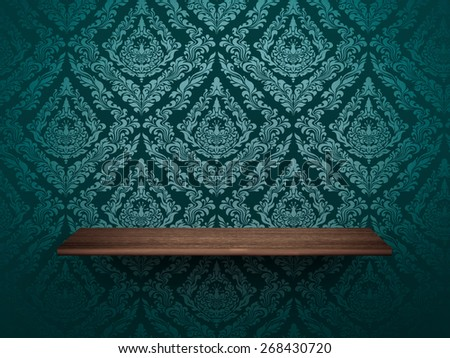 wooden shelf on wall with elegant wallpaper. - stock photo