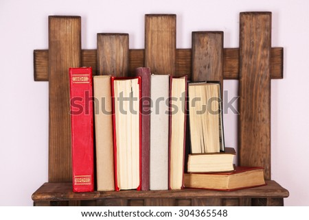 Wooden shelf with books on wall, closeup - stock photo