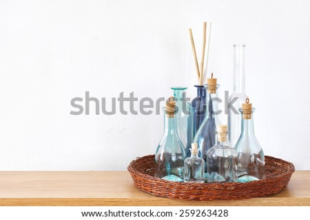 Wooden shelf with decorative bottles against wall. - stock photo