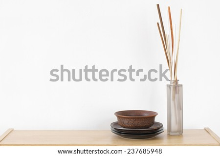 Wooden shelf with decorative elements against white wall. - stock photo