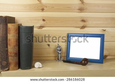 wooden shelf with old books and picture frame for your text. - stock photo