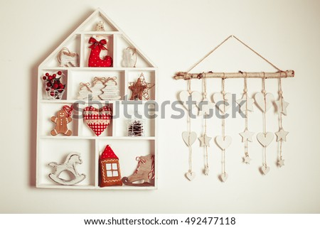 Wooden shelves in shape of cozy home with Christmas decorations