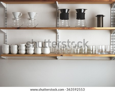 Wooden shelves on white blank wall with japanese ameracan drip coffee makers and blank white and transparent tea, whiskey, coffee cups and glasses