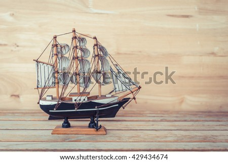 wooden ship model on wood table and wood background, vintage photo - stock photo
