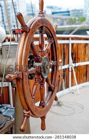 Wooden Ship wheel close up on a sailboat. - stock photo