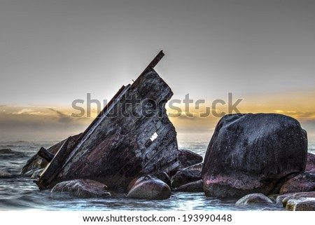 Wooden shipwreck beached on the rocky shore.  Lexington County Park.  Lexington, Michigan.   - stock photo