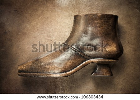 Wooden shoe on leather background