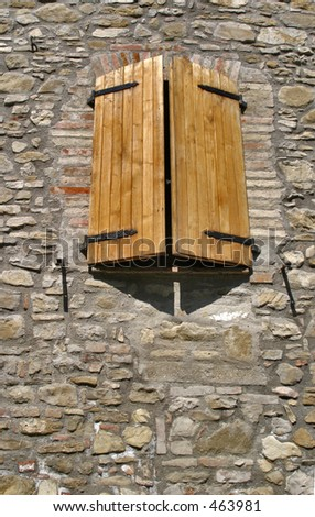 Wooden shutters on a stone building - stock photo